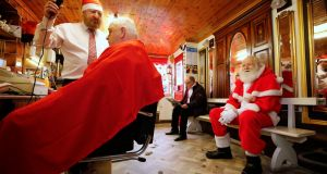 Barber Arthur McGuinness, of McGuinness's Barber Shop in Glasnevin (estd 1910) works on Frank Briscoe of Finglas as an impatient Santa Claus looks on. Photograph: Nick Bradshaw/The Irish Times