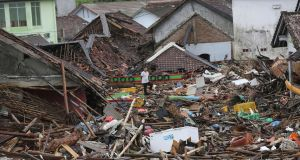 A man inspects the damage at a tsunami-ravaged village in Sumur, Indonesia. Photograph: Tatan Syuflana/AP