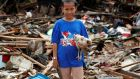 A child holds a chicken while standing among debris at an area affected by the tsunami in  Banten province, Indonesia. Photograph: Jorge Silva/Reuters