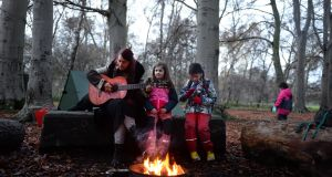 Volunteer Ania Hornowski with Maebh and Zoe, taking part in the Phoenix Forest School, organised by Wild Awake. Photograph: Dara Mac Dónaill / The Irish Times