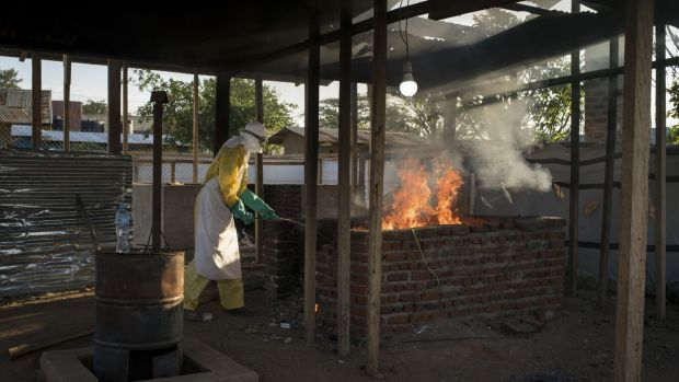 A worker in protective wear burns items that were used in the quarantined area at an Ebola treatment center in Beni, Democratic Republic of Congo in December, 2018. Photograph: Diana Zeyneb Alhindawi/The New York Times