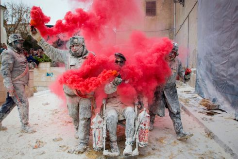 "FOOD FIGHT: Revellers dressed in mock military garb take part in the Els Enfarinats battle in the southeastern Spanish town of Ibi. During this 200-year-old festival, the ""Els Enfarinats"" (those covered in flour) stage a mock coup d'etat as they battle using flour, eggs and firecrackers outside the town hall as part of celebrations of the Day of the Innocents. Photograph: Jaime Reina/AFP/Getty Images"