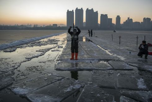 A Chinese worker wears a safety rope as he stands on floating ice while breaking away large blocks of ice that will be used in the making of ice sculptures, on the frozen Songhua River in preparation for the Harbin Ice and Snow Festival. Photograph: Kevin Frayer/Getty Images