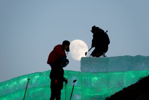 The moon shines as workers prepare an ice sculpture ahead of the Harbin International Ice and Snow Sculpture Festival in Harbin, Heilongjiang province,  REUTERS/Stringer