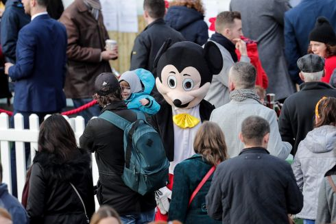 HE'S BEHIND YOU: A child gives Mickey Mouse a miss on the last day of the Leopardstown festival. Photograph: Laszlo Geczo/Inpho
