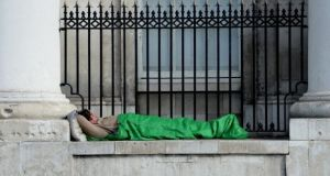 A homeless man sleeps outside the Custom House. Eileen Gleeson, director of the Dublin Region Homeless Executive, said while many loved to help the homeless at Christmas, far fewer wanted homeless services near them all year around. File photograph: Cyril Byrne
