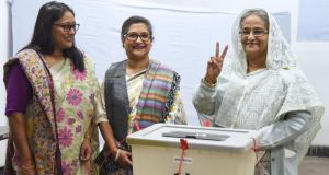 Bangladeshi prime minister Sheikh Hasina (right) flashes the victory symbol after casting her vote, as her daughter Saima Wazed Hossain (left) and her sister Sheikh Rehana (centre) look on at a polling station in Dhaka on December 30th Photograph: AFP/Getty Images