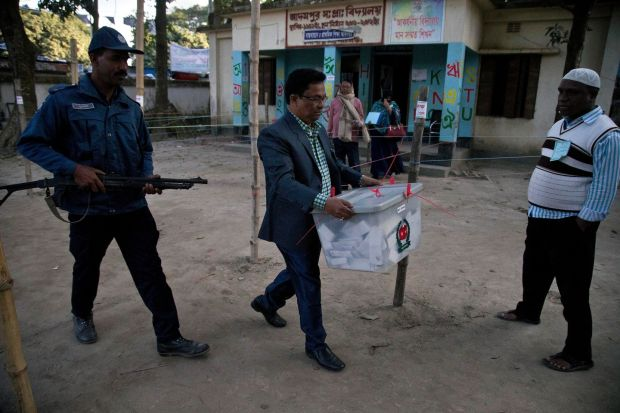 A polling official carries a ballot box after the polling ended at a polling station in the ancient city of Panam Nagar, about 20km southeast of Dhaka in Bangladesh on Sunday Photograph: Anupam Nath/AP