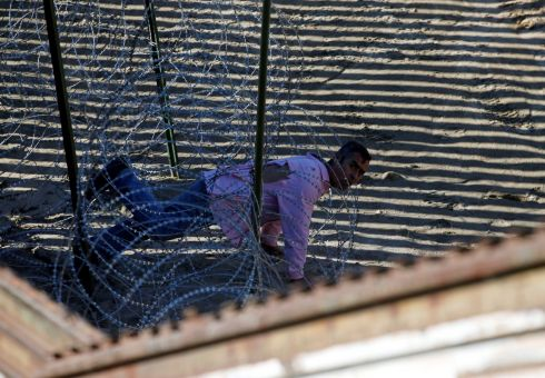 A NEW LIFE: A migrant seeking to enter the United States tries to make his way through razor wire in the border fence in Tijuana, Mexico. Photograph: Mohammed Salem/Reuters