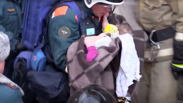 A rescuer carries a 10-month-old child found in the rubble of a Russian apartment block. Photograph: via Reuters TV