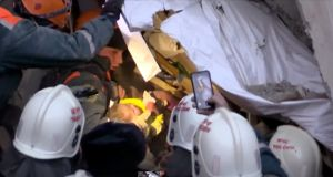 A still image taken from a video footage shows a rescuer carring a 10-month-old child found alive in the rubble of a Russian apartment block that partially collapsed after a suspected gas blast. Photograph: via  Reuters TV