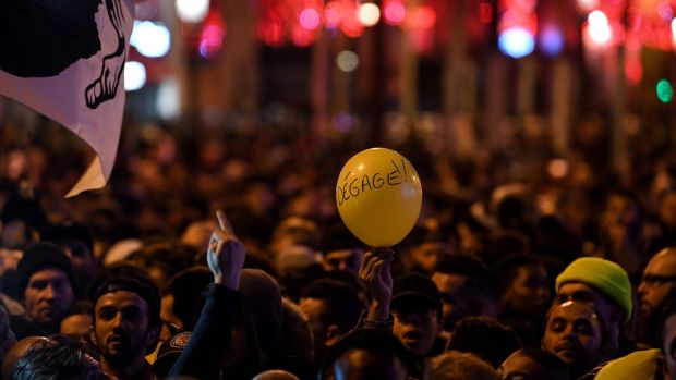 "A Corsican flag and a balloon reading ""Go away"" (meaning Macron) at New Year's Eve celebrations in Paris. Photograph: Getty Images"