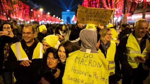 "A yellow vests protester's vest reads, ""Go Macron, President of the Rich, Bleeder of the Poor"" on New Years Eve in Paris. Photograph: EPA"