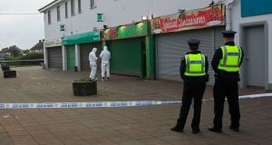 Gardaí at the scene of a shooting at Mizzoni's takeaway in Edenmore, Dublin. Photograph: Gareth Chaney/Collins
