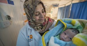 A midwife holds a newborn baby at the maternity hospital in the Zaatari refugee camp. Photograph: Peter Biro/European Union 2018