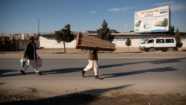Shamal Shirwani, a distant relative of Sima, carries a coffin for her in Kabul, Afghanistan. Photograph: Kiana Hayeri/ The New York Times
