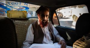 Mullah Jan holds Sima in the back of a taxi as he brings her body   to her hometown.  Photograph: Kiana Hayeri/The New York Times