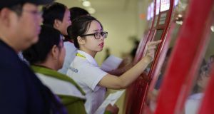 An employee assists travellers with Vietjet Aviation JSC self check-in kiosks at the Tan Son Nhat International Airport in Ho Chi Minh City. Any disruption to the Chinese economy will have serious  consequences for Vietnam. Photograph: Maika Elan/Bloomberg
