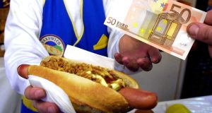 A customer pays for a hot dog in Frankfurt at the start of  2002. The euro's introduction is remembered as an unsentimental quid pro quo. Photograph: AP/Wolfram Steinberg