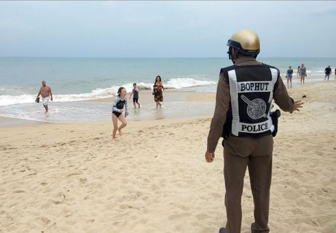 A Thai police officer warns tourists about a swimming ban due to a weather warning at a beach on Koh Samui Island, Surat Thani province, southern Thailand. Photograph Sitthipong Chareonjai/EPA