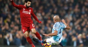 Manchester City's Vincent Kompany  tackles Liverpool's Mohamed Salah during the Premier League game at the Etihad stadium. Kompany received a yellow card for the challenge. Photograph:   Martin Rickett/PA Wire