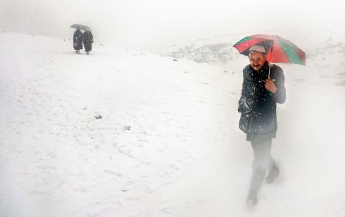 An Afghan in transit during the first snowfall of the year on the outskirts of Kabul, Afghanistan. Photograph: Hedayatullah Amid/EPA
