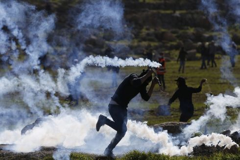 Palestinians demonstrating against Israeli land seizures for Jewish settlements run to avoid tear gas fired by Israeli troops in the village of al-Mughir, north of Ramallah in the occupied West Bank. Photograph: Abbas Momani/AFP/Getty Images