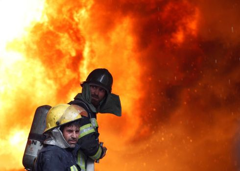 Afghan firefighters try to extinguish a fire at a commercial market in Jalalabad, Afghanistan. Photograph: Parwiz/Reuters