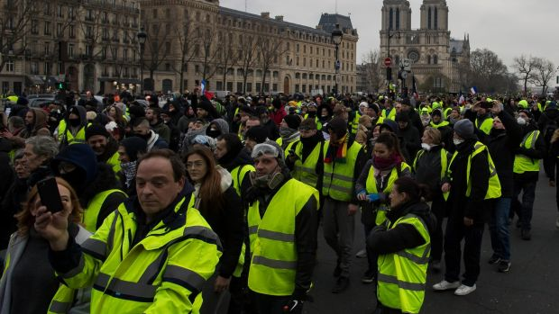 Protesters walk alongside the Seine river during a 'yellow vests' protest in Paris, France. Photograph: Ian Langsdon/EPA