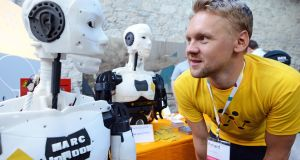 Richard Hulskes, co-founder of Amsterdam-based technology company Wewolver, with a robot at the Web Summit. Photograph: Eric Luke