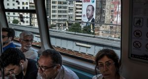 Commuter train passes an election poster for President Recep Erdogan in Istanbul in  June, 2018: people are driven by fear of persecution and economic mismanagement. Photograph:  Sergey Ponomarev/New York Times
