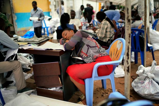 An exhausted electoral commission official rests as results are tallied for the presidential election, at a local results compilation center in Kinshasa on January 6th Photograph: Jerome Delay/AP