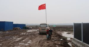 A Chinese flag  on  land secured by Tesla for its gigafactory in Shanghai, China. Photograph: Reuters/Yilei Sun
