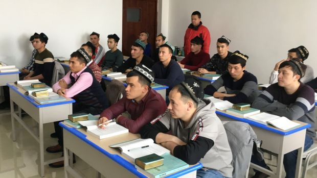 Islamic studies students attend a class at the Xinjiang Islamic Institute during a government organised trip in Urumqi, Xinjiang, China. Photograph: Ben Blanchard/Reuters