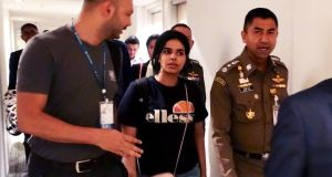 Saudi woman Rahaf Mohammed al-Qanun (18) being escorted by a Thai immigration officer and United Nations High Commissioner for Refugees  officials at the Suvarnabhumi international airport in Bangkok. Photograph:  Thai Immigration Bureau/AFP/Getty Images