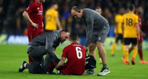 Dejan Lovren receives treatment before leaving the pitch at Molineux. Photograph: Catherine Ivill/Getty Images