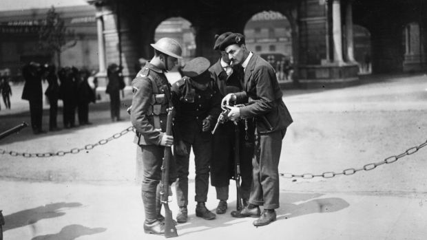 British soldiers watch a member of the Black and Tans, an armed auxiliary force of the Royal Irish Constabulary, reload his .45 revolver, after the burning of the Custom House in Dublin (headquarters of the British Civil Service in Ireland). Photograph: Walshe/Getty Images