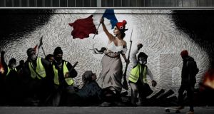 A man with a skateboard passes by a mural by street artist PBOY depicting yellow vest protesters inspired by the 'La Liberte guidant le Peuple' painting in Paris on January 8th Photograph: Philippe Lopez/ AFP/Getty