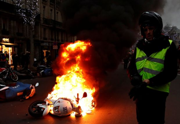 A motorcycle burns during a demonstration by the yellow vest movement at Boulevard Saint Germain in Paris on January 5th Photograph: Gonzalo Fuentes/Reuters