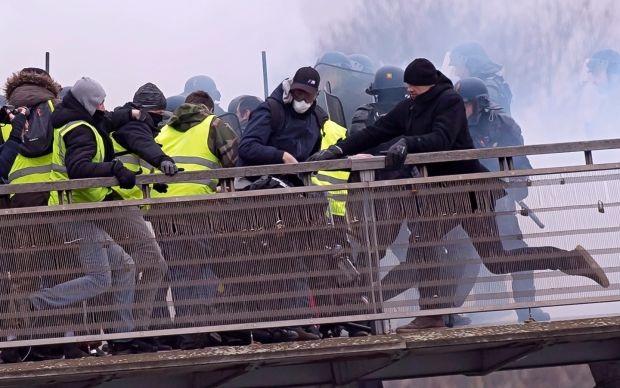 Former French boxing champion, Christophe Dettinger (right in black hat), kicks a French gendarme on the ground during violent clashes on a pedestrian footbridge during a 'gilets juanes' demonstration in Paris on January 5th Photograph: Ian Langsdon/EPA