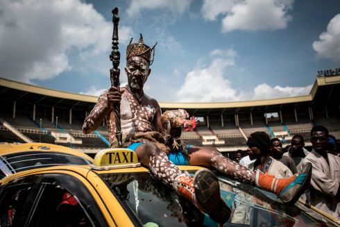 "RIDING HIGH: A Congolese wrestler's ""fetisheur"" sits atop a car as he arrives at the Stade De Martyrs, Kinshasa, Democratic Republic of Congo, for a sports exhibition day. Photograph: John Wessels/AFP/Getty Images"