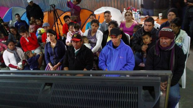 Migrants, part of a caravan of thousands from Central America trying to reach the United States, watch Donald Trump's speech at a shelter in Tijuana. Photograph: Jorge Duenes/Reuters