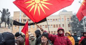 Demonstrators wave old Macedonian flags at a protest against a process of renaming the country North Macedonia. Photograph: Robert Atanasovski/AFP