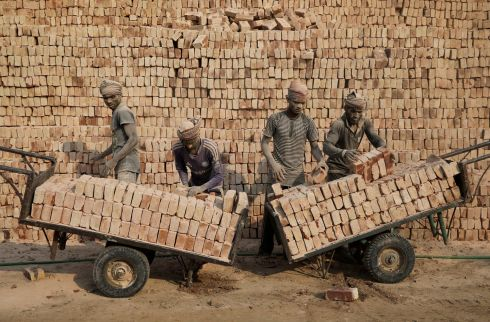 ANOTHER BRICK IN THE WALL: Brick factory workers stack bricks on carts in Dhaka, Bangladesh. Photograph: Mohammad Ponir Hossain/Reuters