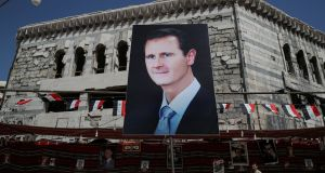 A banner depicting Syrian president Bashar al-Assad in Douma: Unless Syria recovers, millions of Syrian refugees will stay in host countries. Photograph: Marko Djurica