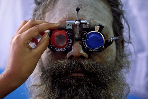 "MAKAR SANKRANTI: A Sadhu or a Hindu holy man gets his eyes tested at a free eye-care camp at a makeshift shelter before heading for an annual trip to Sagar Island for the one-day festival of ""Makar Sankranti"", in Calcutta, India. Photograph: Rupak De Chowdhuri/Reuters"