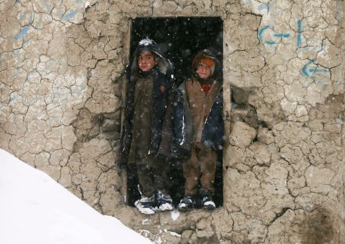 AFGHANISTAN: Internally displaced Afghan boys stand outside their shelter during a snowfall in Kabul, Afghanistan. Photograph: Mohammad Ismail/Reuters