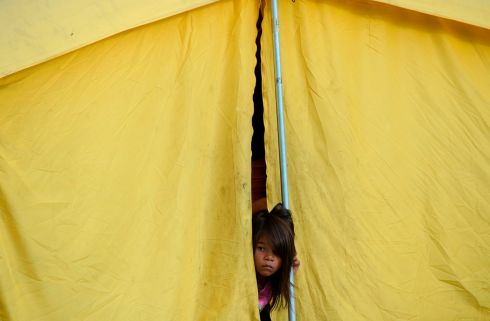 MIGRATION CRISIS: A Venezuelan migrant girl peeps from a tent in a humanitarian camp in Bogota. Photograph: Raul Arboleda/AFP/Getty Images