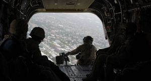 A  US soldier sits in the rear of Chinook helicopter while flying over Kabul. Photograph: Shah Marai/AFP/Getty Images)