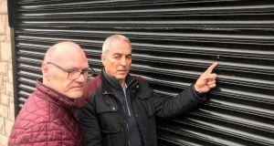 West Belfast MP Paul Maskey, left, and Sinn Féin MLA Pat Sheehan point to a mark made by a bullet during an attack on their constituency office. Photograph: Rebecca Black/PA Wire